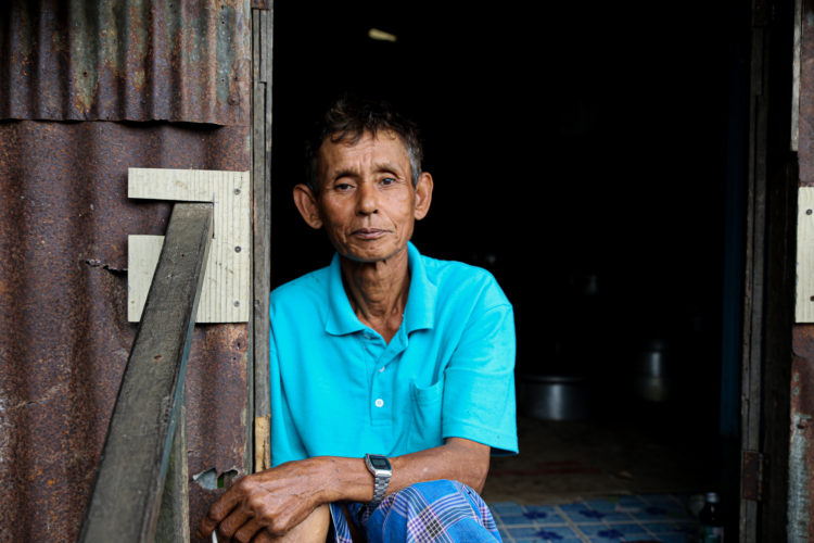Man Sheltering from Rain in Pilok (Kanchanaburi, Thailand)